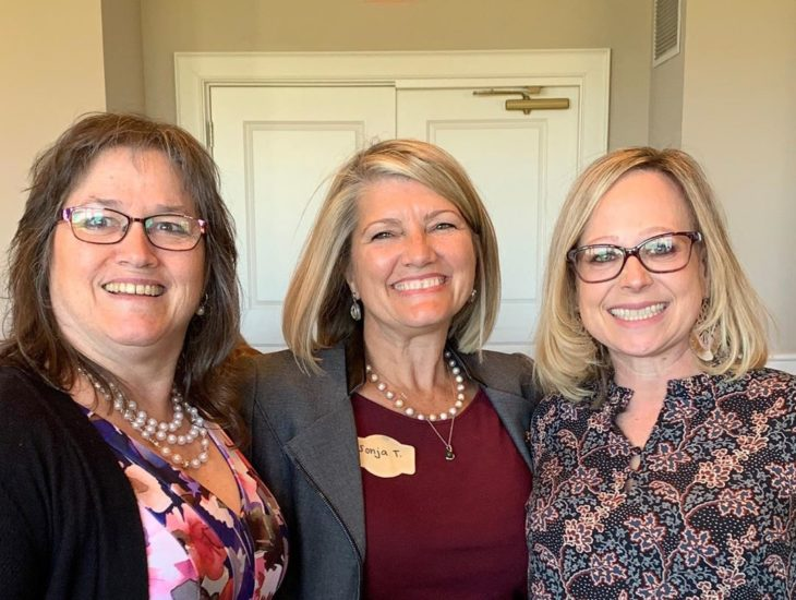 Three alumnae members smile for the camera at a Founders Day event