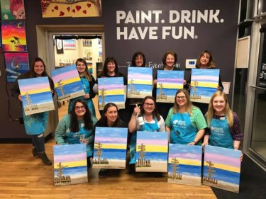 Group of approx. 12 alumnae pose for photo during Night to Reunite with their painted canvases after a wine-and-canvas event.