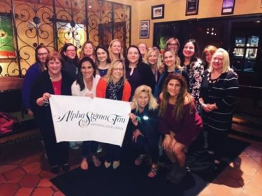 Group of approx. 20 Northern Virginia alumnae pose for photo and hold Alpha Sigma Tau banner