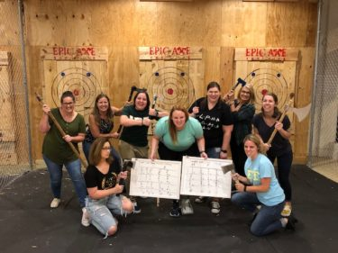 Group of ten alumnae pose for photo during axe-throwing event for Night to Reunite 2019
