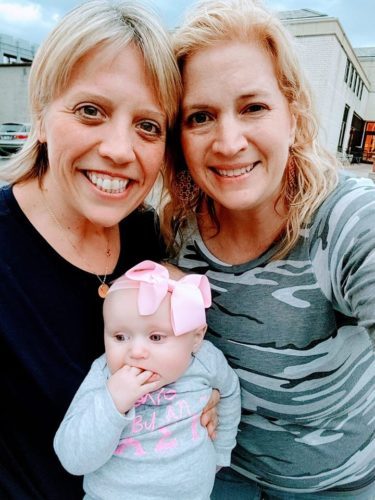Two alumnae connect during Night to Reunite 2019, pose with baby