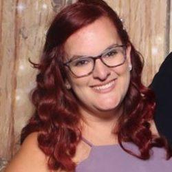 Headshot of Sister Kellie Vehlies. Kellie has reddish-brown hair, glasses, and is wearing a purple dress.