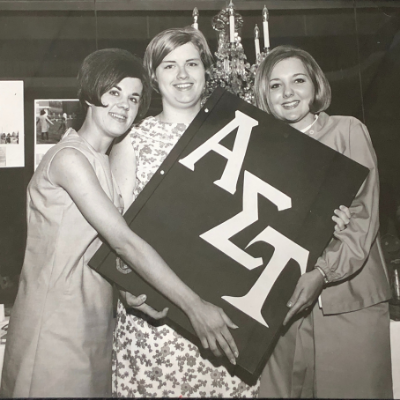 Group of three women in the 1960s at Convention holding a 3-ft book with AΣΤ letters on it.