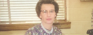 Photo of Rose Marie Schmidt at a school administrator's desk
